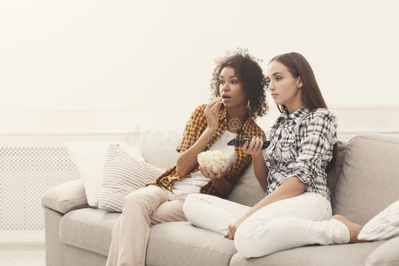 Frightened young women watching TV at home. Frightened young women relaxing and watching scary movie at home, female friends having rest after hard week, copy stock photography