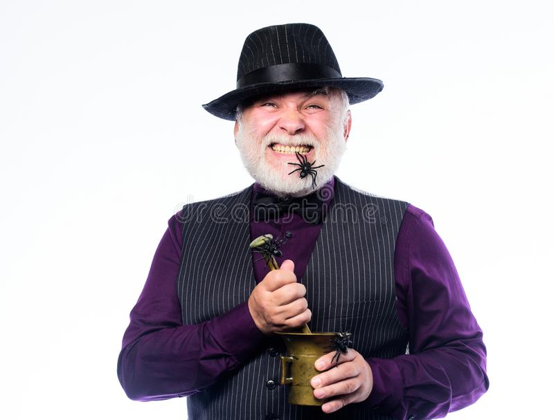 Frightening bartender. Weird old bartender with gray beard and spider. Preparing magic drink. Halloween concept. Strange stock image
