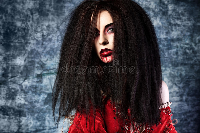 Frightening evil. Portrait of a bloodthirsty female vampire royalty free stock photography