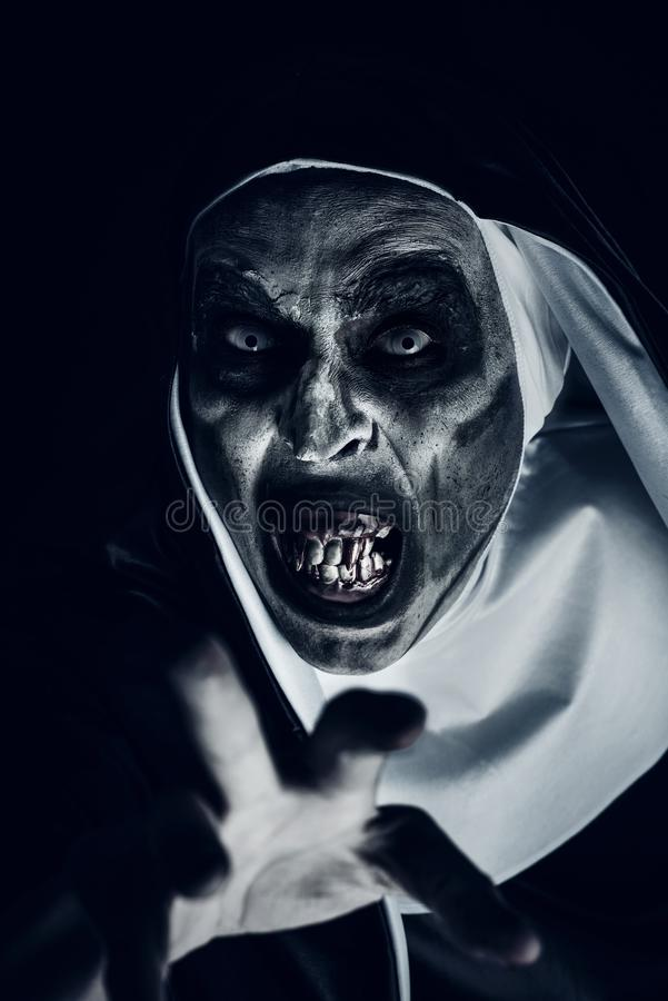 Frightening evil nun with bloody teeth. Closeup of a frightening evil nun, with bloody teeth and scary eyes, wearing a typical black and white habit, doing a royalty free stock images