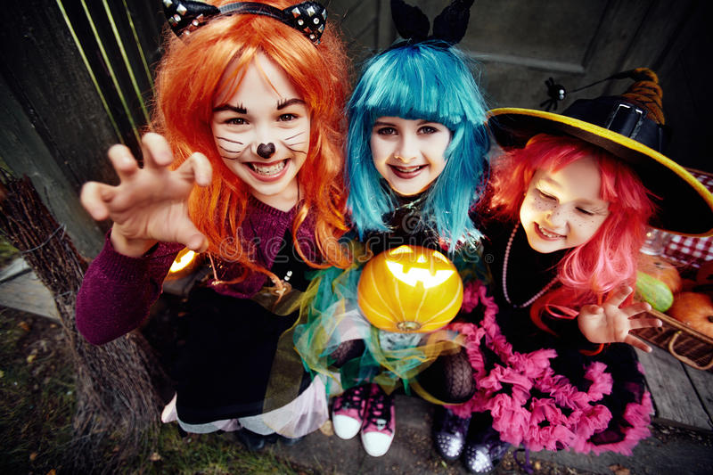 Frightening gesture. Frightening girls in wigs with jack-o-lantern stock photography