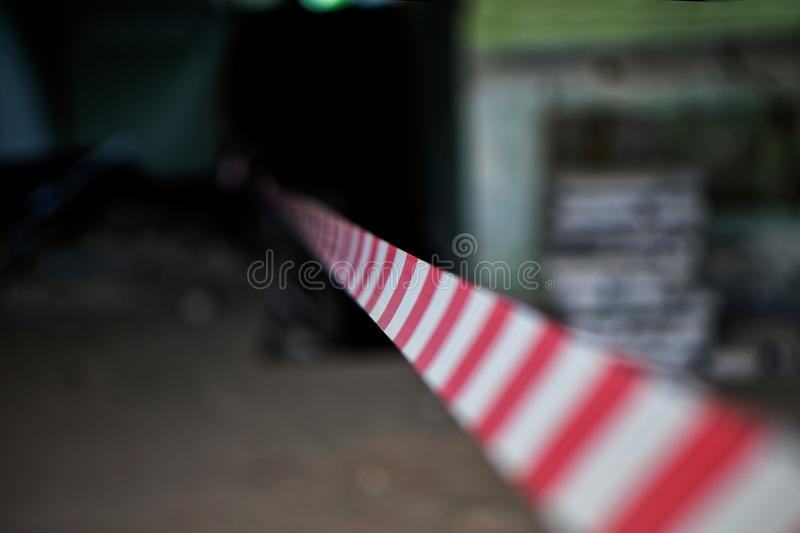Frightening ominous picture with caution tape - fire prevention and protection equipment. Crime scene. Shallow depth of field. Defocus royalty free stock photography