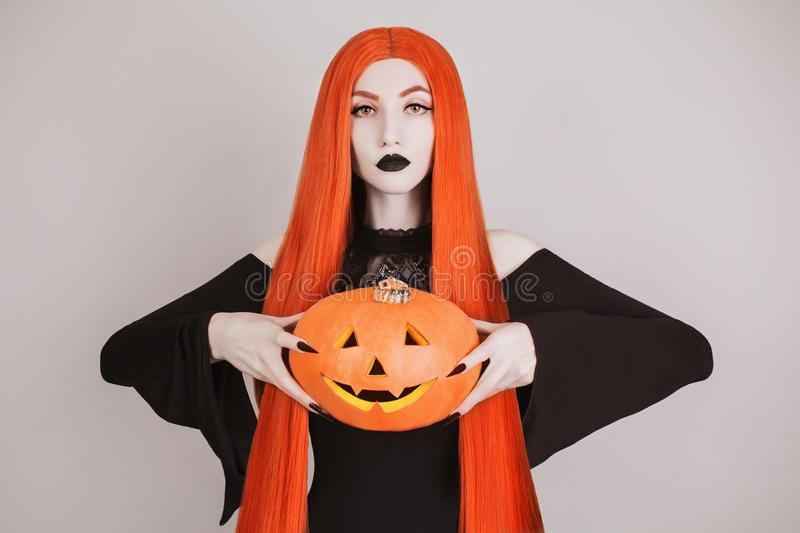 Frightful halloween costume. Mystical witch with black lips. Gothic woman witch with red hair in black dress holding pumpkin. Goth royalty free stock photos