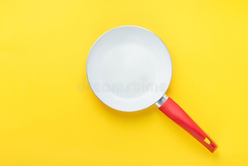Frigideira cerâmica branca com o punho vermelho no fundo amarelo brilhante Imagem denominada criativa Utensílios da cozinha da en imagem de stock royalty free