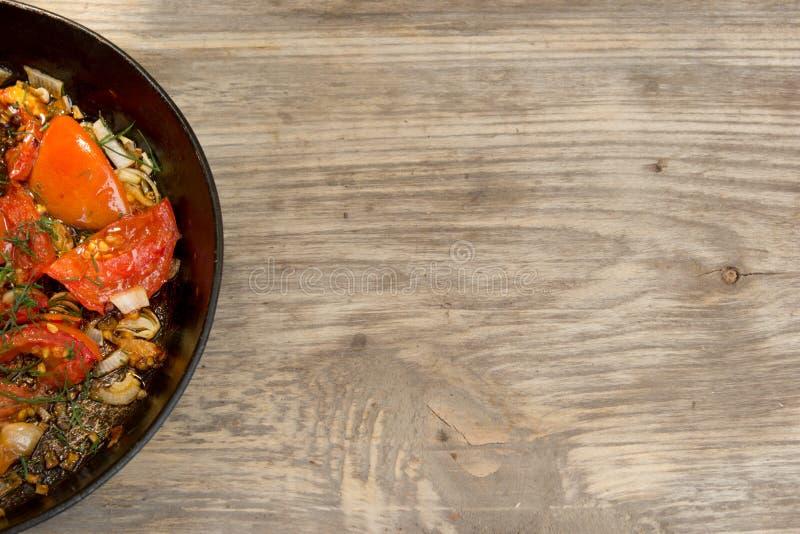 Frigideira com ovos mexidos e tomates na tabela rústica de madeira imagens de stock royalty free