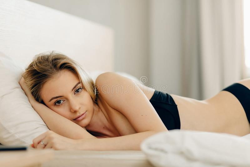 Frigile blond girl looking at camera while staying in bed after sleep stock image