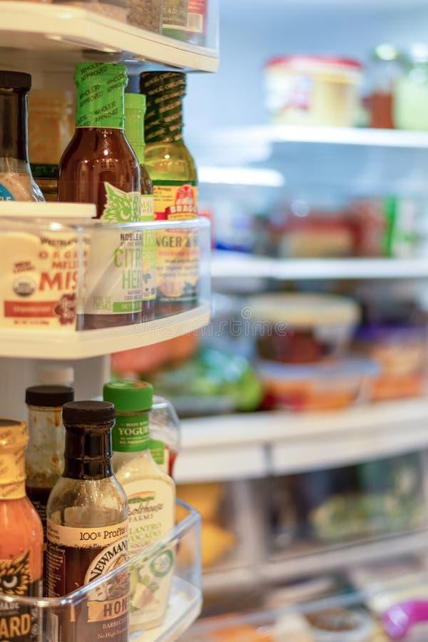 Frigorífico aberto com uma variedade de alimentos frescos e condimentos fotografia de stock royalty free