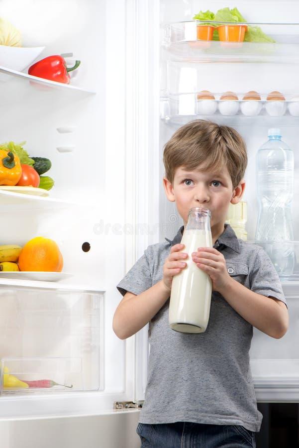 Frigorifero aperto del latte alimentare del piccolo ragazzo sveglio vicino fotografie stock
