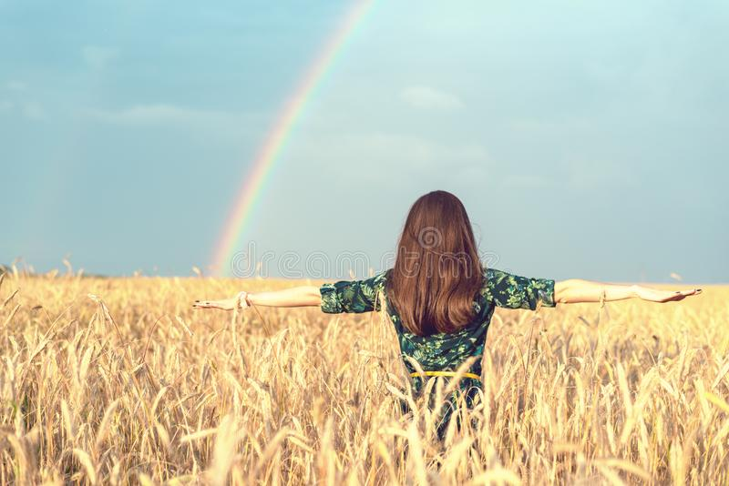 Frihet Lycklig le kvinna med öppna händer i vetefält med guld- spikelets som ser upp på himlen på regnbågebakgrund arkivfoton