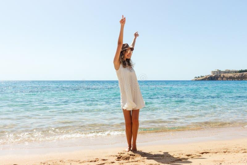 Frihetskvinna i fri lyckasalighet på stranden Le den lyckliga flickan i vit sommar klä i semester utomhus arkivbilder