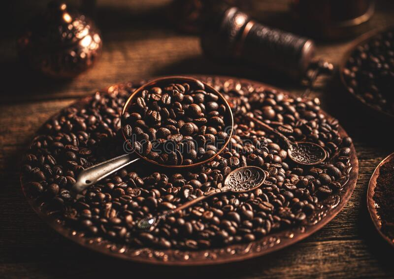 Frijoles de café en placa de cobre imagenes de archivo
