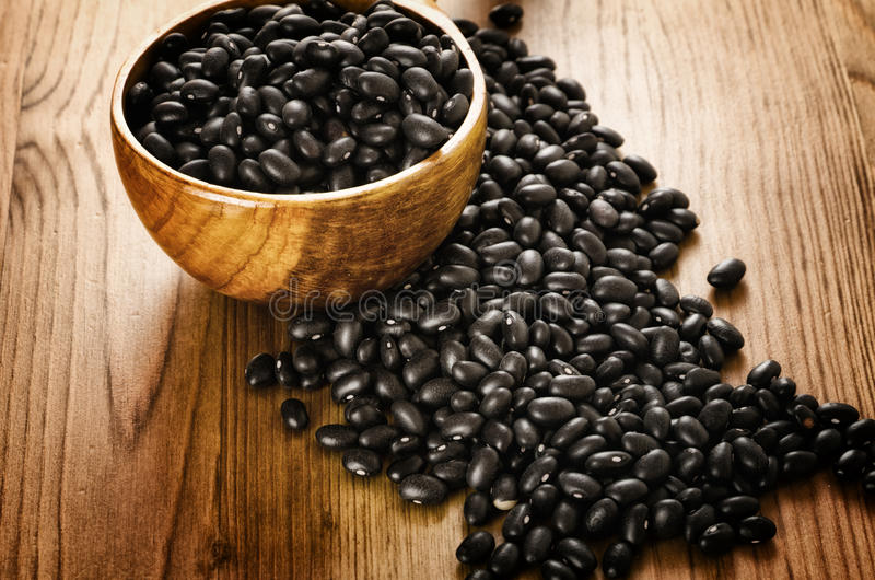 Black beans on wooden background. Frijoles, mexican black beans, on wooden background, biologic culture stock photo