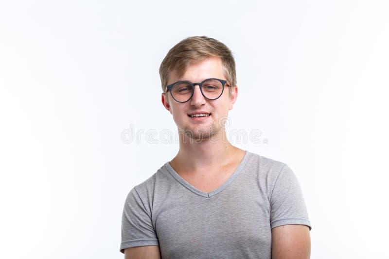 Friki, educación, concepto de la gente - el hombre joven sobre el fondo blanco mira como él es un empollón imagenes de archivo