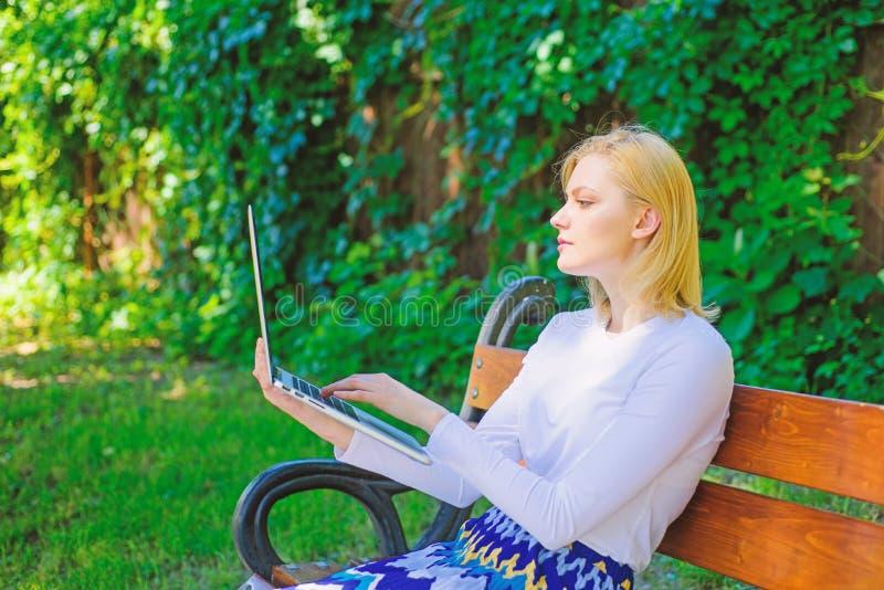 Frilans- fördelar Kvinnan med bärbara datorn arbetar utomhus- grön naturbakgrund Damfreelanceren som in arbetar, parkerar royaltyfri bild