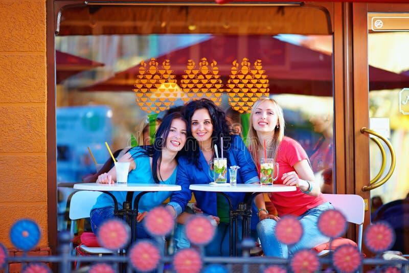 Frinds hermosos que se sientan en terraza del café del verano imagenes de archivo