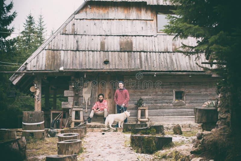 Frineds junto delante de casa de madera vieja foto de archivo libre de regalías