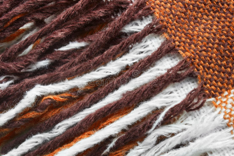 Fringe. Wool brown and white fringe closeup as a background stock photos