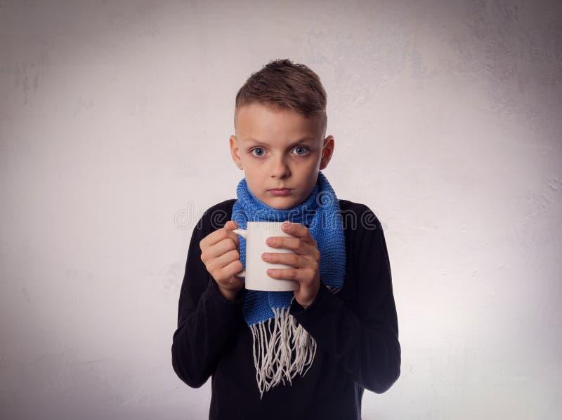 Frio do menino, e chá morno da bebida fotografia de stock