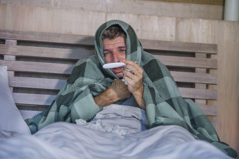 Frio doente e gripe de sofrimento indispostos de encontro em casa desperdiçados e esgotados do sentimento da cama do homem que es fotografia de stock