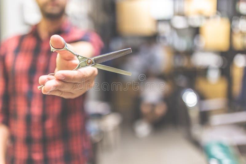 Frisör för modern man som rymmer skarp yrkesmässig sax på frisersalongen arkivbild