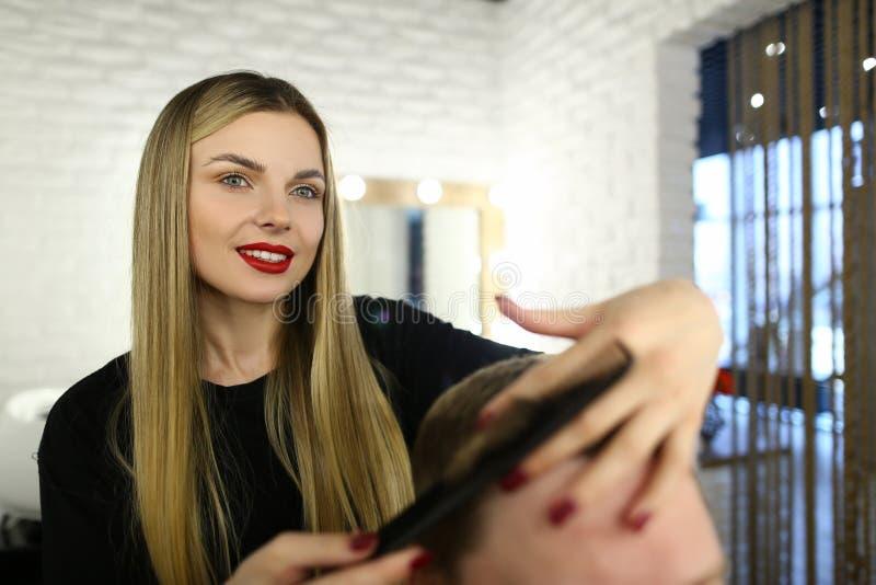 Frisör Making Haircut för ung kvinna med hårkammen arkivfoto