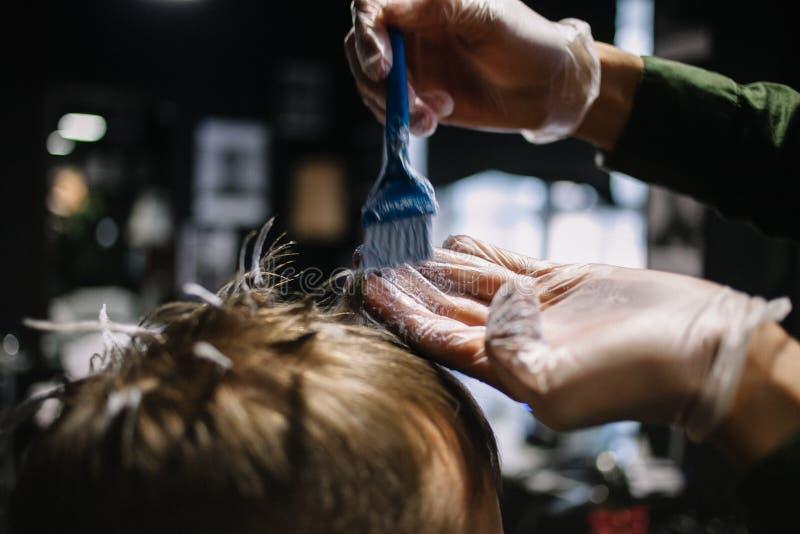 Frisör med en borste som applicerar hårfärg Att färga i barberaren shoppar arkivbilder