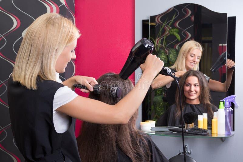 Frisör med kvinnligt hår för hårtork- och hårborsteuttorkning i s arkivfoto