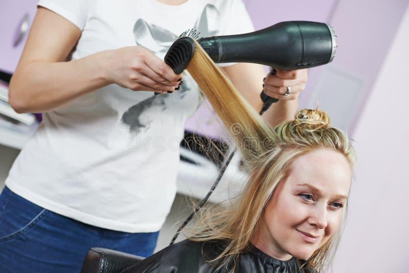 Frisör på arbete. Dryeing hår fotografering för bildbyråer