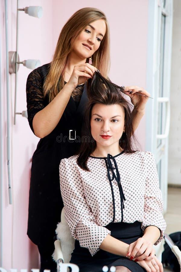 frisör på arbete - frisören gör håret av en härlig ung brunett till klienten i skönhetsalong royaltyfri foto