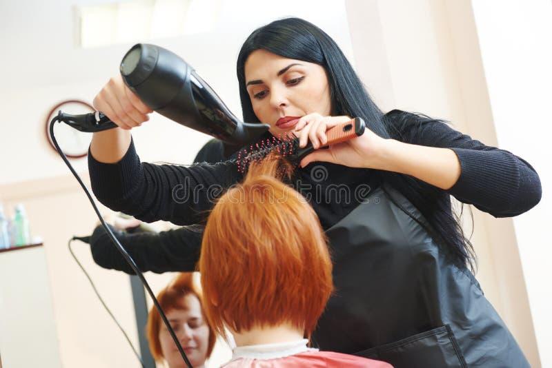 Frisör på arbete torkande hår royaltyfri foto