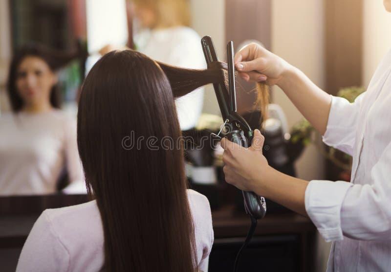 Frisör som använder krullande järn på skönhetsalongen royaltyfria foton