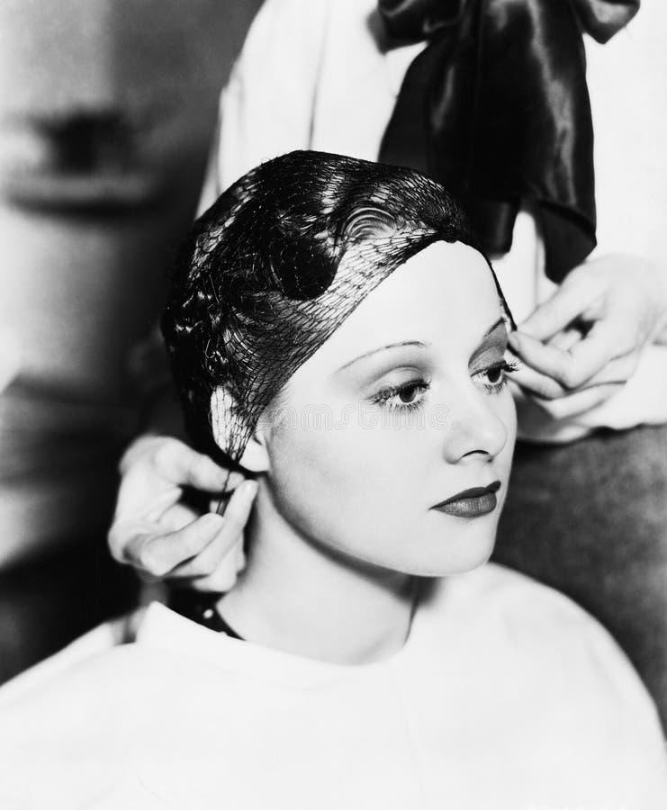 Frisör som binder netto för hår på ung kvinnas hår (alla visade personer inte är längre uppehälle, och inget gods finns Leverantö royaltyfria bilder