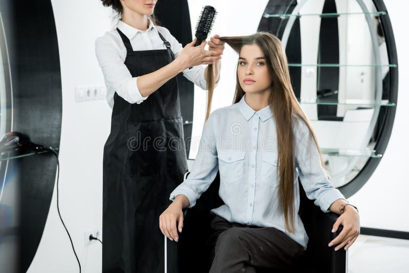 Frisör som borstar hår av kvinnan royaltyfria foton
