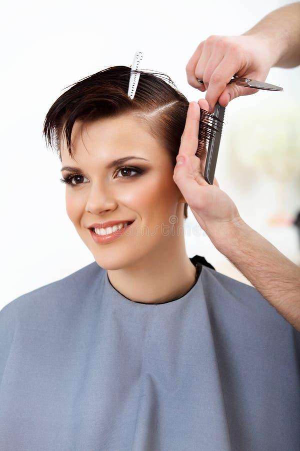 Frisör som gör frisyren Brunett med kort hår i salong arkivfoton