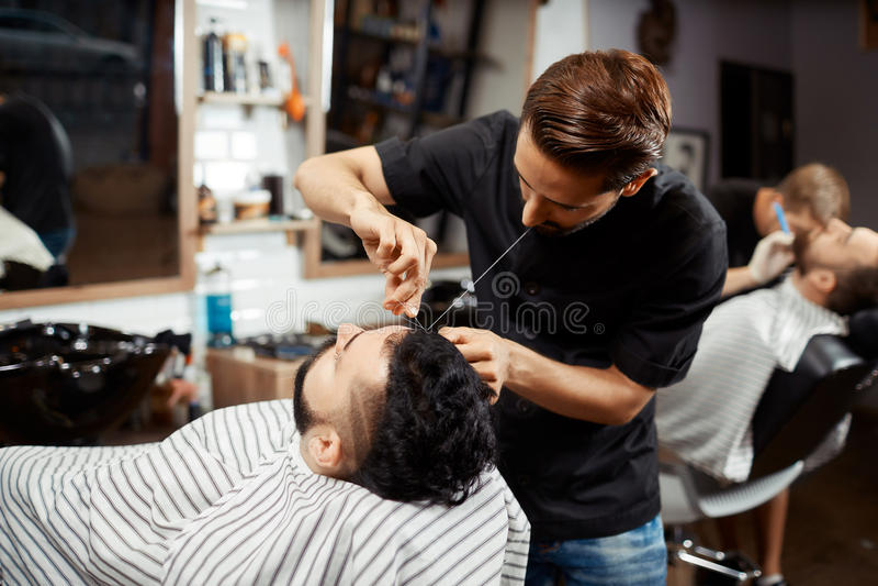 Frisör som gör korrigerings- och klippbröd i modern frisersalong arkivfoto