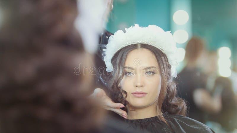 Frisör som gör lockigt hår för härlig modell arkivfoton
