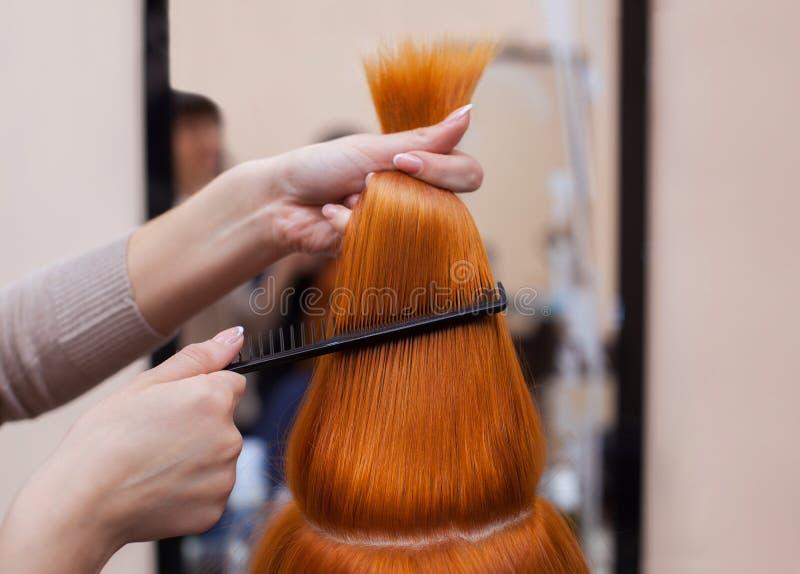 Frisör som kammar hennes långa röda hår av hans klient arkivfoto