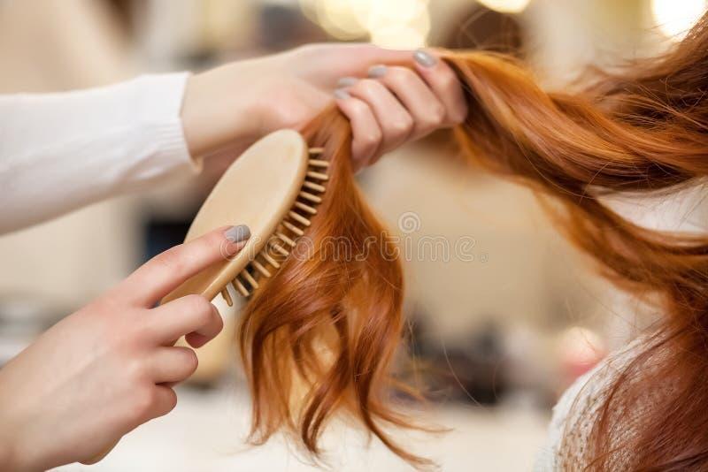 Frisör som kammar hennes långa röda hår av hans klient i skönhetsalongen royaltyfria foton