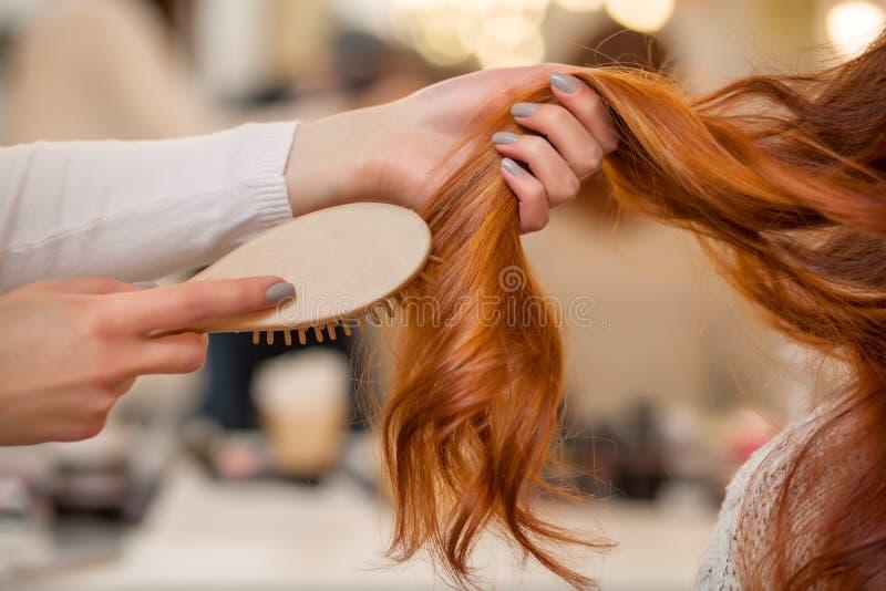 Frisör som kammar hennes långa röda hår av hans klient i skönhetsalongen arkivfoto