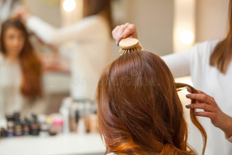 Frisör som kammar hennes långa röda hår av hans klient i skönhetsalongen arkivbilder