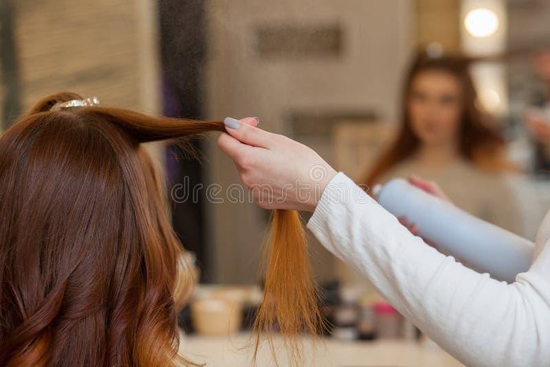 Frisör som kammar hennes långa röda hår av hans klient och stänkhårspray i en skönhetsalong arkivfoton