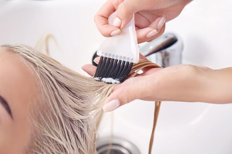 Frisör som sätter maskeringen på hår för kvinna` s royaltyfria foton