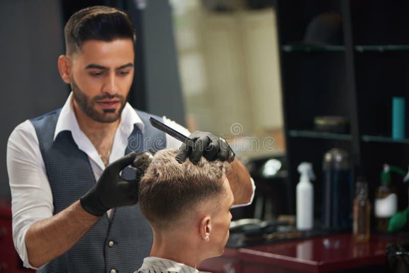 Frisör som ser klienten och klipper hans frisyr royaltyfria bilder