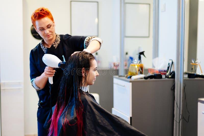 Frisör som torkar kvinnligt kundhår med handtorken i hårsalong royaltyfri foto
