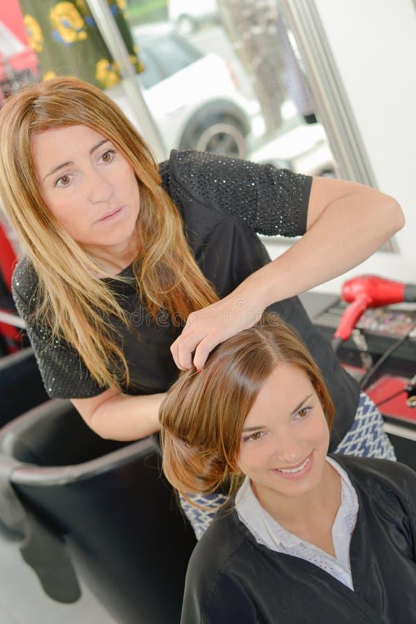 Frisör som utformar hår för dam` s arkivbilder