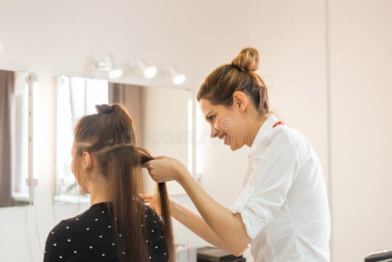 Frisörcoiffeuren gör frisyren arkivfoto