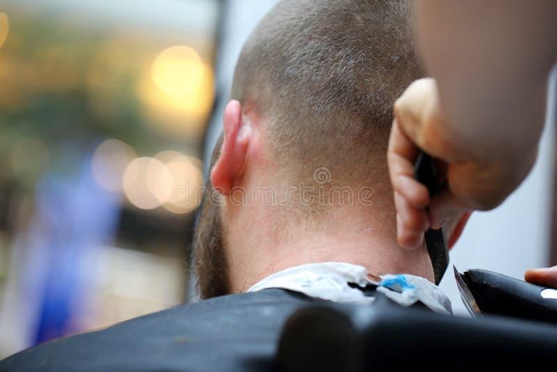 Frisörcoiffeuren gör frisyren med den elektriska beskäraren och c arkivfoto