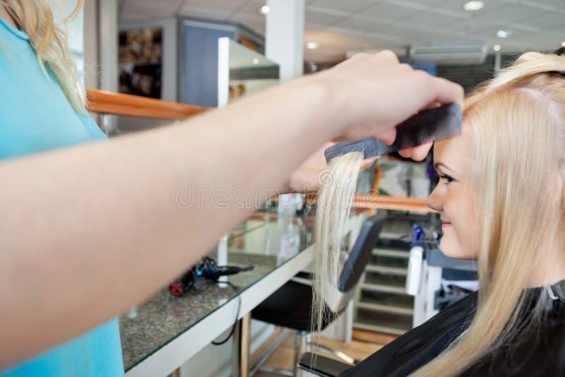 FrisörCombing Hair Of kvinna arkivbilder
