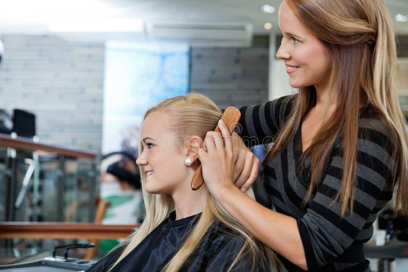FrisörCombing Hair Of kvinnlig arkivbilder