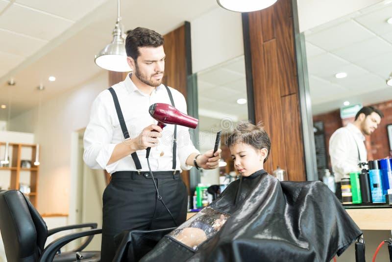 FrisörDrying Hair Of gossebarn i Barber Shop fotografering för bildbyråer